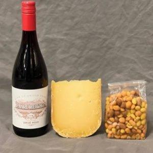 Geschenk met een fles rode wijn borrelnootjes en een stukje oude kaas